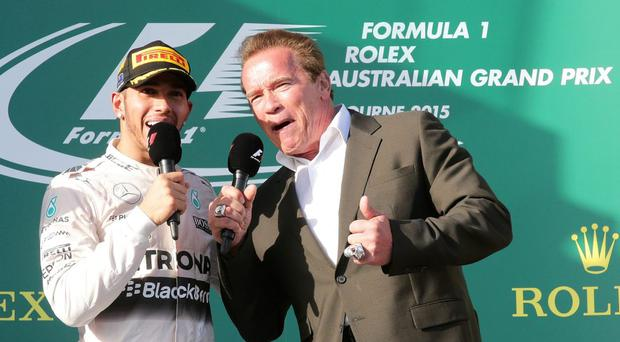 Mercedes driver Lewis Hamilton speaks with actor Arnold Schwarzenegger on the podium after winning the season-opening Australian Formula One Grand Prix at Albert Park in Melbourne