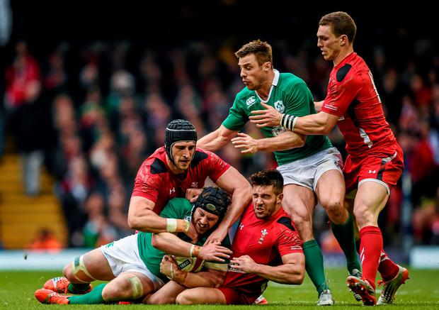 Sean O'Brien with the support of his Ireland team-mate Tommy Bowe, is tackled by Luke Charteris, left, and Rhys Webb and their Wales team-mate George North, right