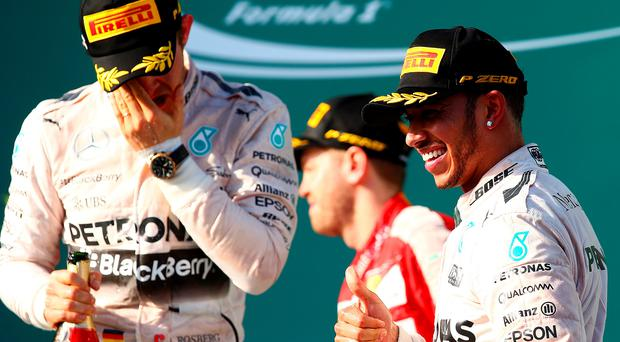 Lewis Hamilton of Great Britain and Mercedes GP celebrates on the podium next to Nico Rosberg of Germany and Mercedes GP after winning the Australian Formula One Grand Prix
