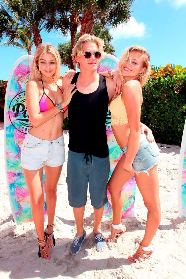 Victoria's Secret PINK models Gigi Hadid (L) and Rachel Hilbert (R) and singer Cody Simpson attend the Ultimate Spring Break Bash hosted by Victoria's Secret PINK Nation