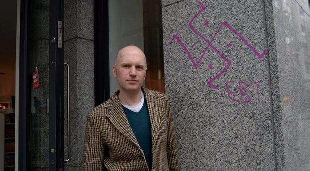 Bob Johnston, owner of The Gutter Book shop, with graffiti on wall of shop. Cow's Lane, Temple Bar, Dublin. Picture: Caroline Quinn