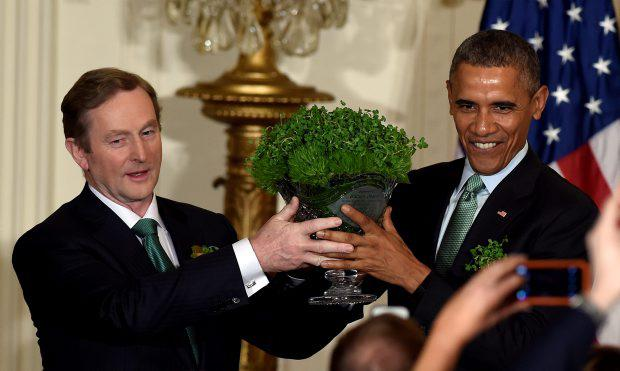 President Barack Obama, right, and Irish Prime Minister Enda Kenny, left, hold up a bowl of shamrocks during a reception in the East Room of the White House in Washington, Tuesday, March 17, 2015