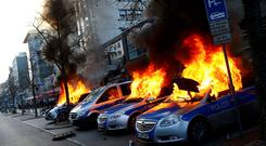 Four German police cars set on fire by anti-capitalist protesters burn near the European Central Bank (ECB) building hours before the official opening of its new headquarters in Frankfurt