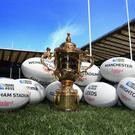 The Webb Ellis Cup sits on the pitch with rugby balls showing the venues which will be used in the England 2015 Rugby World Cup