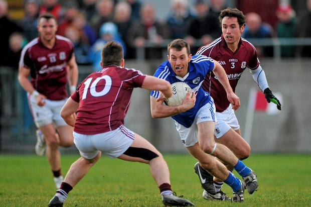 Niall Donoher, Laois, in action against Sean Denvir and Finian Hanley, Galway
