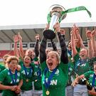 Irish women's rugby captain Niamh Briggs lifts the Six Nations Trophy as her team-mates celebrate a victory that completed a memorable double for Irish fans at the weekend