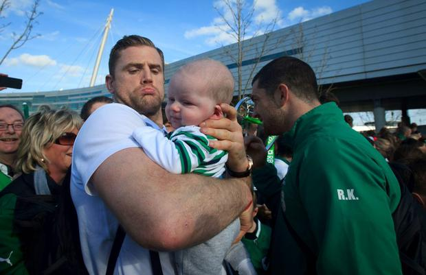 22/03/2015 Jamie Heaslip & Rob Kearney with Irish fan Charlie Hassett 3 months from Tipperary after the Irish Rugby side arrived at Dublin Airport following their 6 Nations Championship win Photo: Gareth Chaney Collins