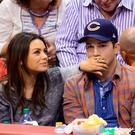 Mila Kunis (L) and Ashton Kutcher attend a basketball game