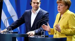 German Chancellor Angela Merkel and Greek Prime Minister Alexis Tsipras address a news conference following talks at the Chancellery in Berlin REUTERS/Hannibal Hanschke
