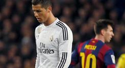 Barcelona's Lionel Messi (R) and Real Madrid's Cristiano Ronaldo react during their Spanish first division