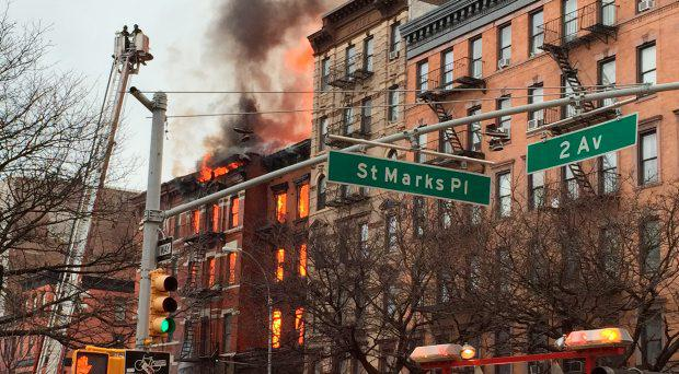 New York City firefighters work the scene of a large fire and a partial building collapse in the East Village neighborhood of New York on Thursday, March 26, 2015. Orange flames and black smoke are billowing from the facade and roof of the building near several New York University buildings