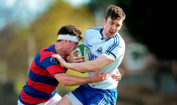 Darren Sweetman, Cork Constitution, is tackled by Aidan Darcy, Clontarf