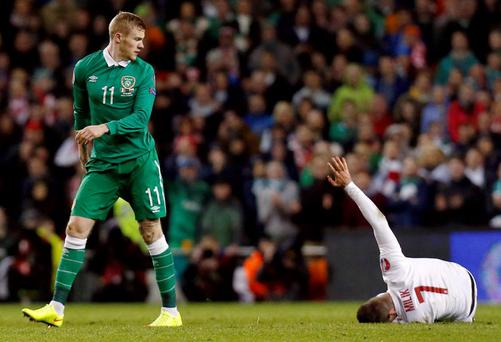 Ireland's James McClean looks towards Poland's Arkadiusk Milik as he lies on the pitch after his tough challenge Reuters / Cathal McNaughton