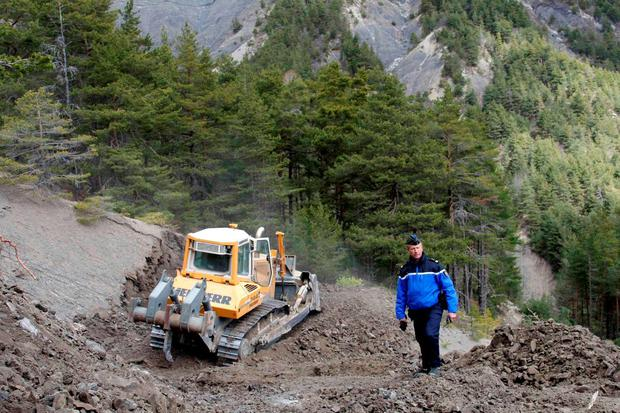 French Gendarme Bruno Hermignies stands by a bulldozer clearing a path to the crash site of the Germanwings Airbus A320 in the mountains, near Seyne-les-Alpes, French Alps. Photo: Reuters