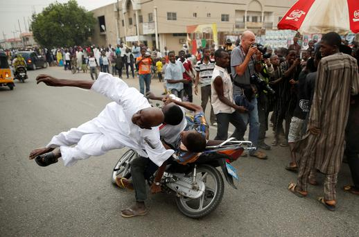 Over-excited motor-cycling supporters of the presidential candidate Muhammadu Buhari collide with another supporter during celebrations in Kano yesterday. Photo: Reuters