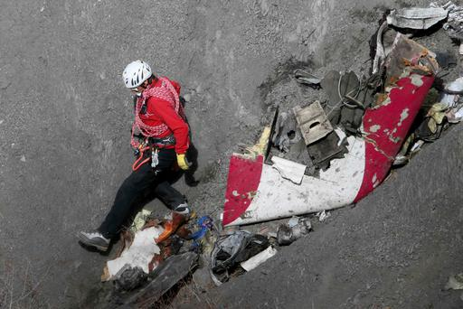 A French rescue worker inspects the remains of the Germanwings Airbus A320 at the site of the crash, near Seyne-les-Alpes, French Alps in this March 29, 2015, file photo. Americans fear pilots purposely crashing an airliner as much as they are afraid of a hijacking, and over a quarter are more scared of flying than they were before a copilot crashed a jet in France last week, killing 150 people, a Reuters/Ipsos poll found. REUTERS/Gonzalo Fuentes/Files