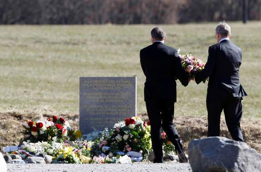 CEO of Germanwings Thomas Winkelmann and Lufthansa CEO Carsten Spohr, left, arrive with a wreath of flowers at a stone slab erected as a monument in memory of the victims, near the site of the Germanwings jet crash, in Le Vernet, France, Wednesday, April 1, 2015. (AP Photo/Claude Paris)