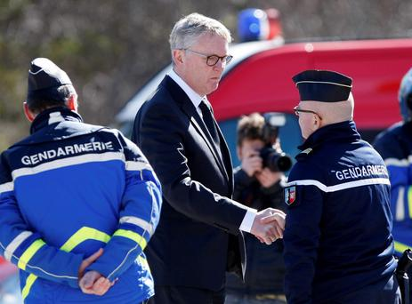 CEO of Germanwings Thomas Winkelmann, centre, shakes hands with French gendarmes near the site of the Germanwings jet crash, in Le Vernet, France, Wednesday, April 1, 2015. (AP Photo/Claude Paris)