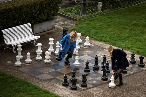 Russian journalists play a game of giant chess in a courtyard of the Beau Rivage Palace Hotel in Lausanne, Switzerland (AP Photo/Brendan Smialowski, Pool)