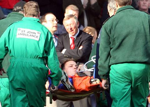 Manchester United's Alan Smith is stretchered off as manager Alex Ferguson (C) looks on during their FA Cup Fifth Round soccer match at Anfield on February 18, 2006. REUTERS/Phil Noble