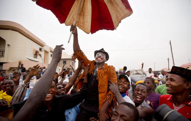 A supporter of opposition candidate Muhammadu Buhari, center, who is dressed up to represent and mock current President Goodluck Jonathan, celebrates an anticipated win for his candidate, in Kano, Nigeria (AP Photo/Ben Curtis)