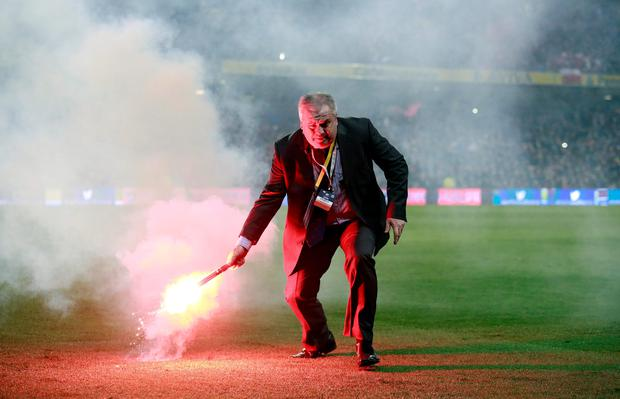 A match official lifts a flare from the pitch