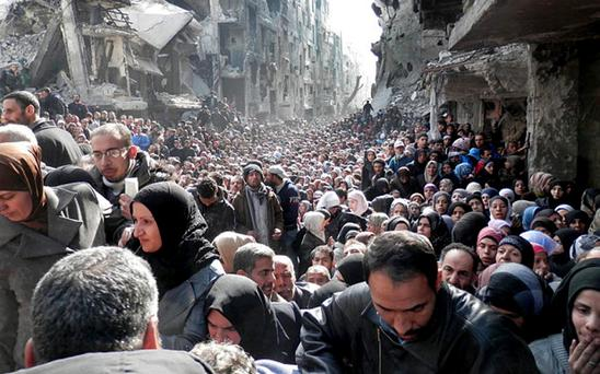 Residents of the besieged Palestinian camp of Yarmouk queuing to receive food supplies Credit: UNRWA