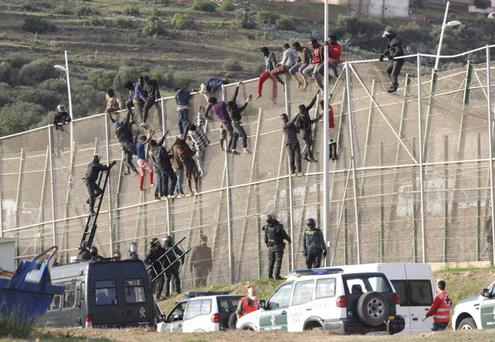 Dozens of immigrants attempting to cross a border fence in Melilla, a Spanish city near the northern coast of Africa Credit: F.G. Guerrero