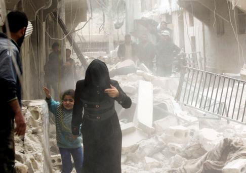 A woman holds the hand of a girl as they move away from a site hit by what activists said was a barrel bomb dropped by forces loyal to Syria's President Bashar al-Assad in Aleppo's al-Fardous district. REUTERS/Rami Zayat