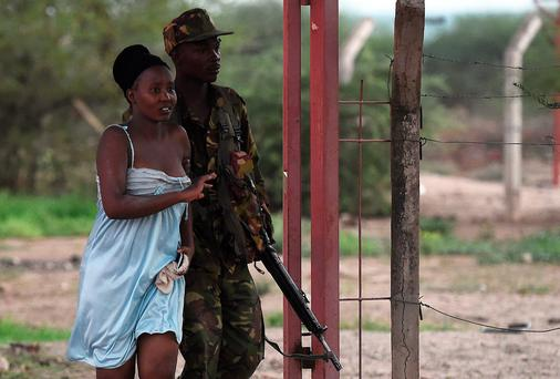 A member of the security forces escorts a student out of Garissa University campus in Garissa after an attack by Somalia's Al-Qaeda-linked Shebab gunmen (Getty Images)