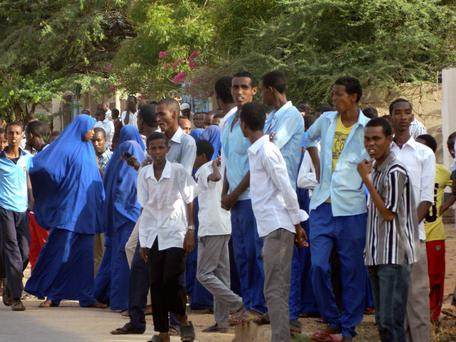 Students gather and watch from a distance outside the Garissa University College after an attack by gunmen, in Garissa, Kenya (AP Photo)