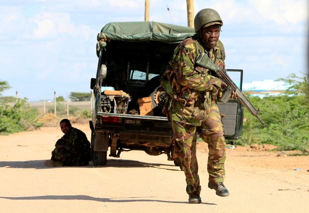 A Kenya Defense Force soldier runs for cover near the perimeter wall where attackers are holding up at a campus in Garissa April 2, 2015