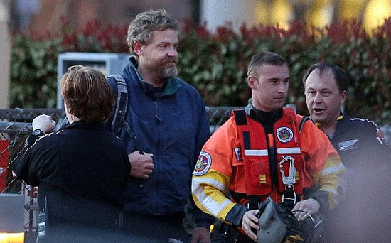 Louis Jordan, second from left, walks from the Coast Guard helicopter to the Sentara Norfolk General Hospital in Norfolk, Va.