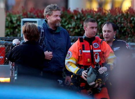 Louis Jordan, second from left, walks from the Coast Guard helicopter to the Sentara Norfolk General Hospital, after being found off the North Carolina coast. (AP Photo/The Virginian-Pilot, Steve Earley)