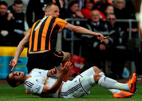 Hull City's Irish midfielder David Meyler (L) is sent off for this tackle on Swansea City's English defender Kyle Naughton