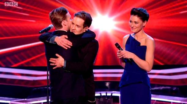 The Voice UK winner Stevie McCrorie embraces coach Ricky Wilson as Emma Griffiths looks on
