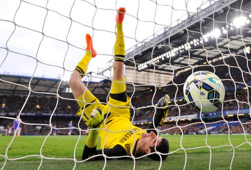 Chelsea goalkeeper Thibaut Courtois falls after failing to keep out Charlie Adam's long range strike for Stoke City
