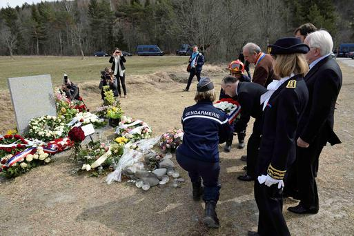 French Interior Minister Bernard Cazeneuve (2ndL) is helped by a gendarme as he places a wreath by a stele in memory of the victims of the Germanwings Airbus A320 crash REUTERS/Lionel Bonaventure/Pool