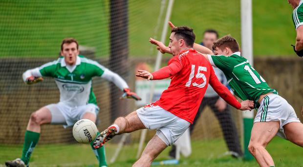 Louth's Derek Maguire attempts a shot on goal despite the efforts of Limerick's Cillian Fahy
