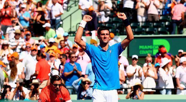 Novak Djokovic of Serbia celebrates to the crowd after his three set victory against Andy Murray of Great Britain in the mens final during the Miami Open