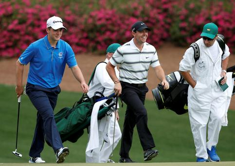Bradley Neil of Scotland (L) walks up the tenth fairway with Rory McIlroy