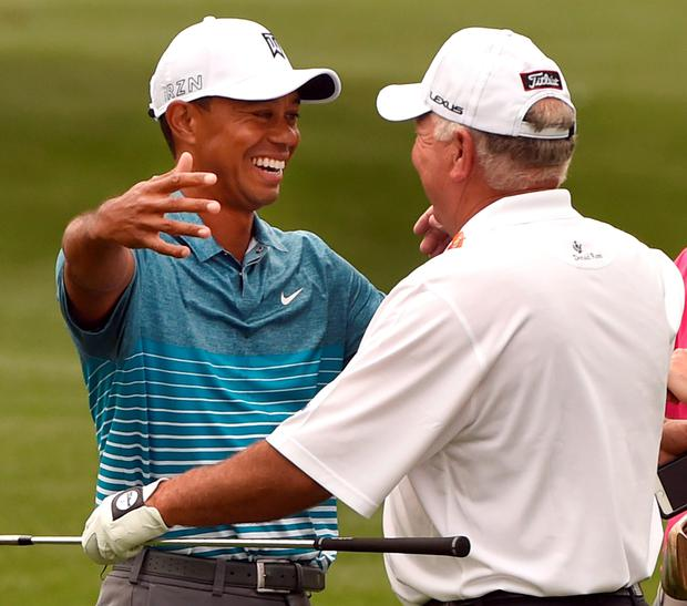 Tiger Woods hugs Mark O'Meara on the practice range at Augusta as they prepare for the Masters