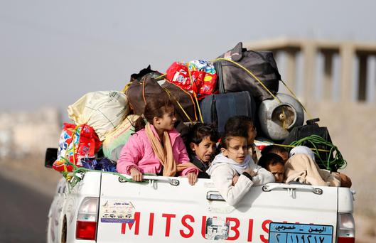 Children ride on the back of a pick-up truck with their luggage as they flee Saudi-led air strikes in Sanaa April 6, 2015. REUTERS/Khaled Abdullah