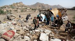People gather around the wreckage of a house destroyed by an air strike in the Bait Rejal village, west of Yemen's capital Sanaa. REUTERS/Khaled Abdullah
