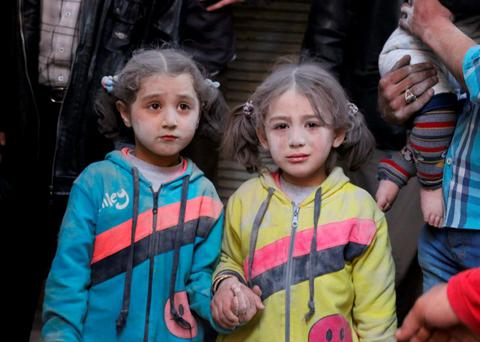Girls who survived what activists said was a ground-to-ground missile attack by forces of Syria's President Bashar al-Assad, hold hands at Aleppo's Bab al-Hadeed district. Photo: Reuters