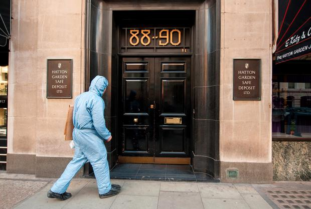 A police forensics officer enters the Hatton Garden Safe Deposit company, in London Photo credit: Dominic Lipinski/PA Wire