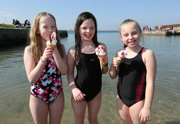 From left to right are, Caoimhe Coffey, 9, with her twin Aibhe Coffey, aged 9, from Ballinteer and Anna Louise Finn, 8, from Naas enjoy an ice cream at Sandycove beach in Dublin. Picture credit: Damien Eagers