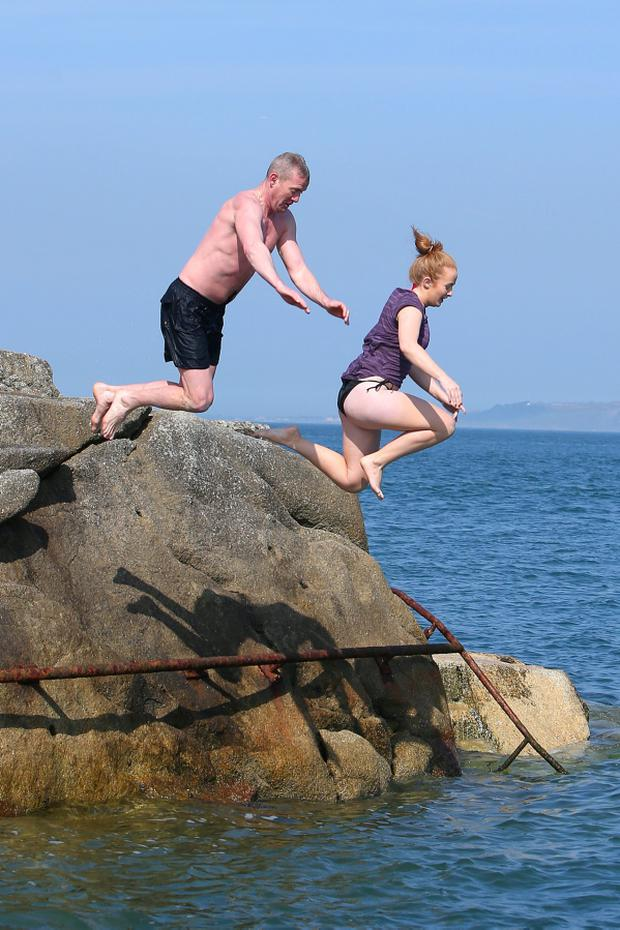 Phil Kelly, from Loughlinstown and Niamh Corrigan, 20, from Rataoth, Co, Meath dive into the water at the Forty Foot in Sandycove, Dublin. Picture credit: Damien Eagers 7/4/2015