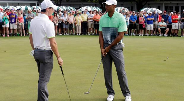 Rory McIlroy talks with Tiger Woods on the practice green before the Masters golf tournament Wednesday, April 8, 2015, in Augusta, Ga. (AP Photo/Darron Cummings)
