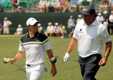 Rory McIlroy of Northern Ireland (L) walks up the ninth fairway with Phil Mickelson of the U.S. during first round play of the Masters golf tournament at the Augusta National Golf Course